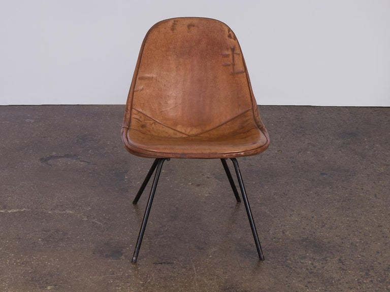 An exemplary variation of an otherwise definitive design, this Eames wire chair sits on a low lounge height base. It features original leather in a gorgeously aged patina. The rich, smooth, coffee colored leather fosters a cohesive contrast with the