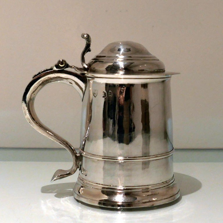 A rare and extremely collectable early Georgian silver cylindrical 'ladies' tankard and cover elegantly plain formed in design. The body tapers at the angles and sits on a 'skirt' foot. The hinged domed lid has an ornate cast thumbpiece and the