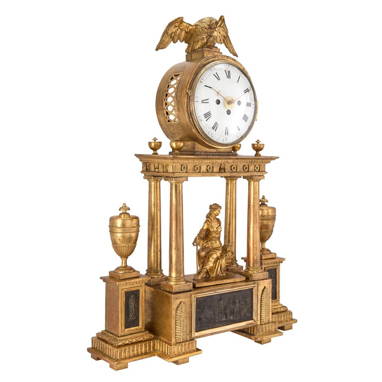A handsome early 18th century Austrian giltwood and mecca blind mans clock. The clock , with two separate chimes, one for quarter hour and the other for hour. Raised on a solid base with pedestals on each side displaying a mecca plaque supporting an
