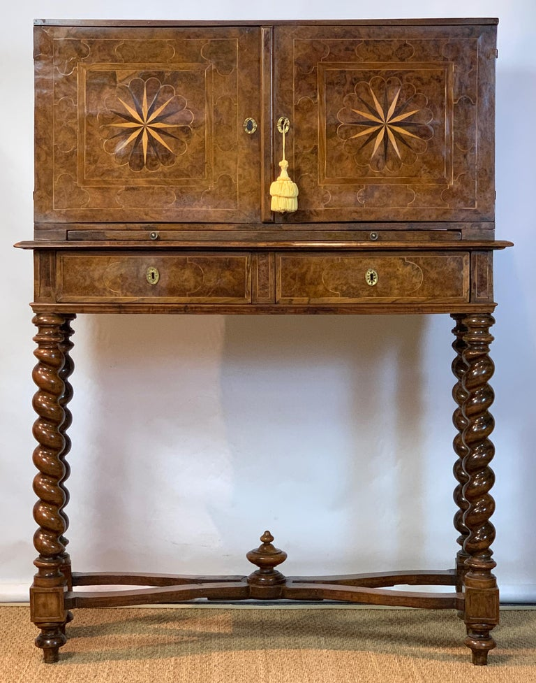 A handsome early 18th century Italian burl walnut chest on stand with elaborate inlay throughout resting on barley twist supports linked by carved stretchers. The interior of the cabinet is later fitted for use as a spirit cabinet with compartments