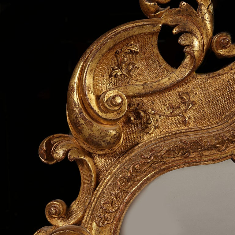 A fine early 18th century German giltwood pier mirror, the gilt frame with burnished and hatched reserves in carved gesso overlaid with strapwork, the crest with a flamboyant arrangement of bold scrolls and acanthus ornament around a framed scallop