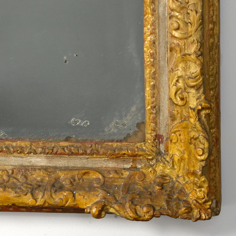 A large early 18th century carved parcel gilded frame, housing a period mercury glass mirror plate.