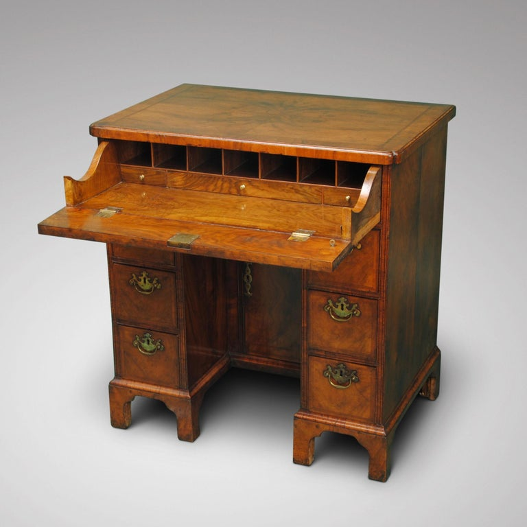 A walnut kneehole desk with quarter veneered top above an unusual fitted secretaire drawer. The kneehole with two banks of drawers all retaining the original brass handles.