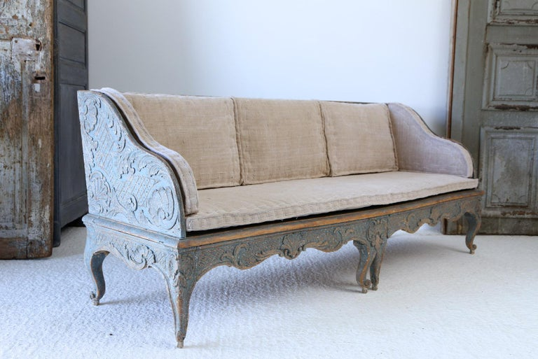 A fine example of a 18th century Swedish carved wood sofa with original paintwork and later upholstery. The carving on the sofa is extremely good with lots of detail