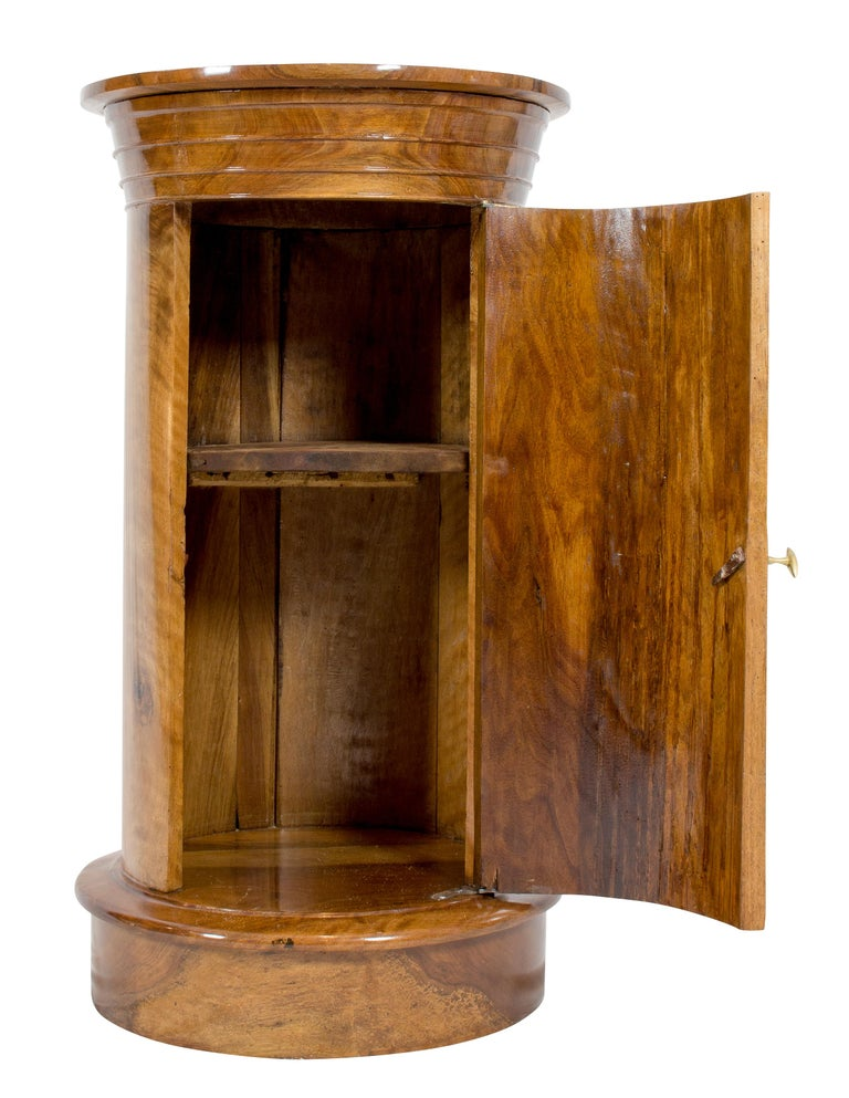 Very rare drum cabinet from the Biedermeier period, circa 1820. The round cabinet was made of solid walnut wood. The proportions of the capital and the base are very harmonious, so that the furniture has a very clean beautiful design. The opening
