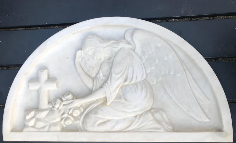 Hand-carved kneeling angel in relief.  This mourning angel by a grave is entirely hand-carved out of marble. This early 20th century Christian work of art can be used hanging on the wall or standing on a shelf. The natural posture of this carved