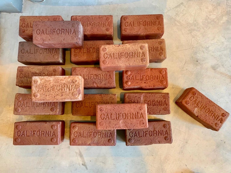 Interesting bricks from the early 1900s, used to pave the streets in California. Each brick is stamped 'California.' Super unique piece of California history. Cool table top object, or can be used as a group to create a door entrance platform. 40