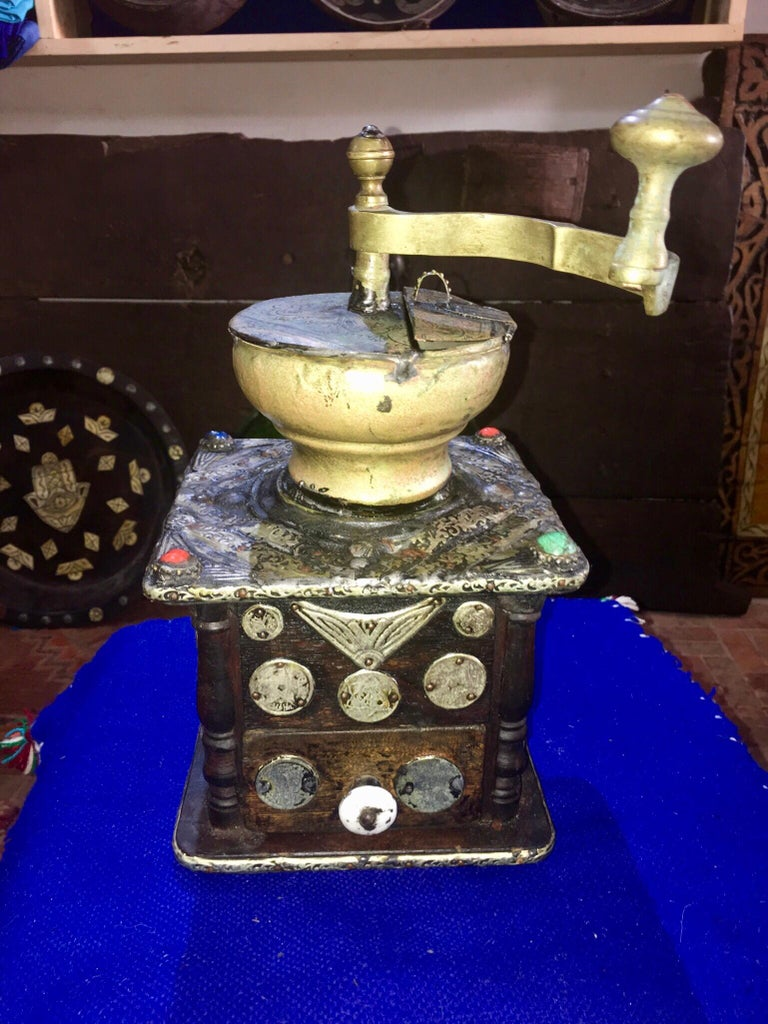 This antique hand-crank grinder is made of ebony wood, with hand-engraved silver melange adornment, hand carved camel bone embellishments, and numerous antique coins. Entirely handmade, this grinder was used by southern Morocco nomads while