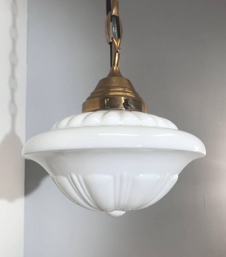 Highly stylish glass-art pendant light.   This unique and stunning 1920s Art Deco pendant is of museum quality and condition. The combination of the beautifully designed, clean white shade and the excellent brass chain is a match made in heaven.