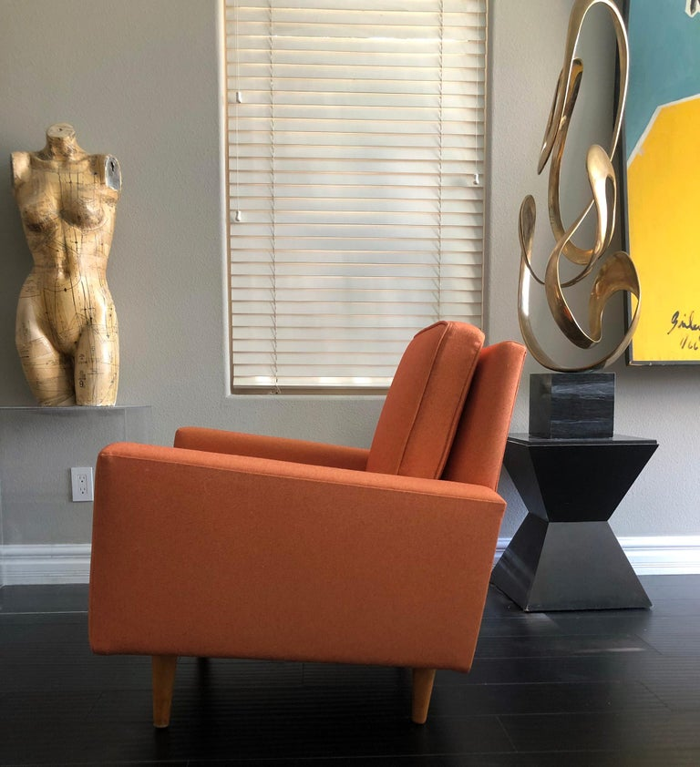 This lounge chair is truly stunning. This early Florence Knoll lounge chair features cone shaped birch legs, and fresh tangerine colored tone-on-tone period appropriate fabric.   With its clean lines, angular body, and modern shape, this lounge