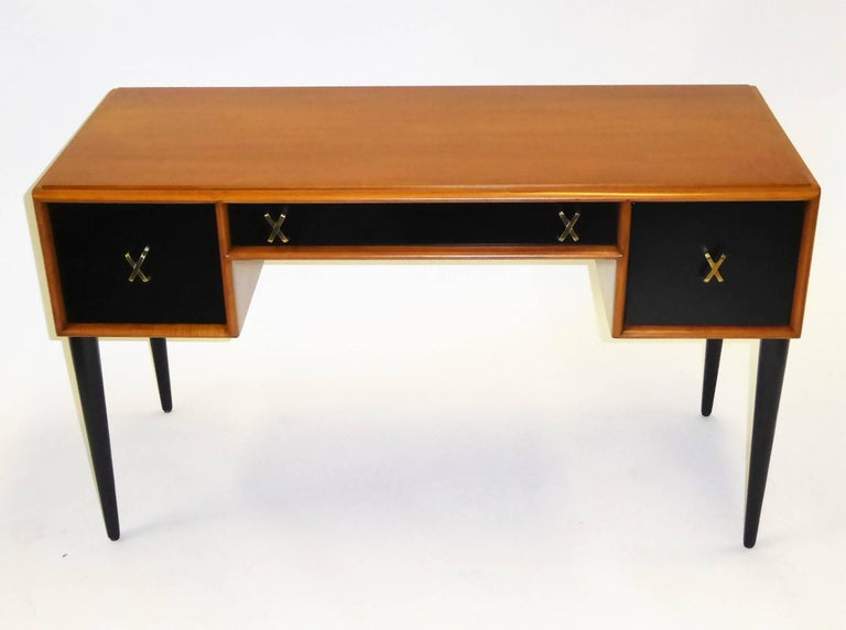Rarely seen exquisite Paul Frankl designed mid century modern desk or vanity in cherry and black satin lacquer with brass X-pulls. With a John Stuart store tag and made by Johnson Furniture Company in the early 1950s. Beautiful figured wood, finely