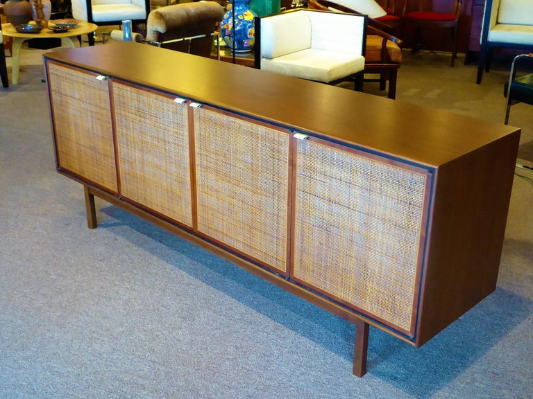 A beautifully designed and constructed credenza by Founders Furniture, probably a Jack Cartwright design, it features a figured walnut case body with cane front doors and leather tab pulls supported by a rectilinear base. Doors conceal two