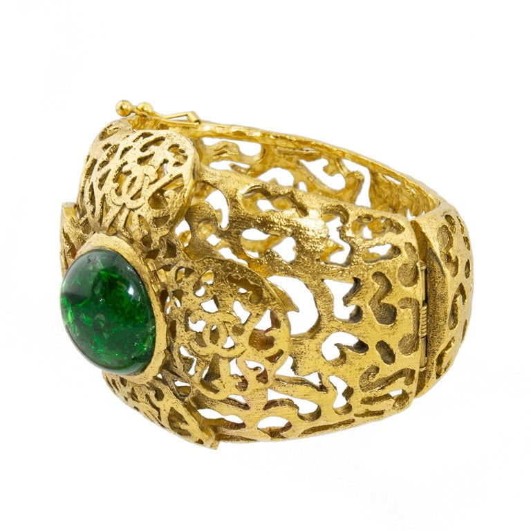 Early 1980s Chanel gold tone cage cuff with filigree details. Large emerald green crackle effect poured glass stone in centre of classic Chanel 4 leaf flower motif with cc logo embedded in filagree design. Two bracelet catch clasps on one side open