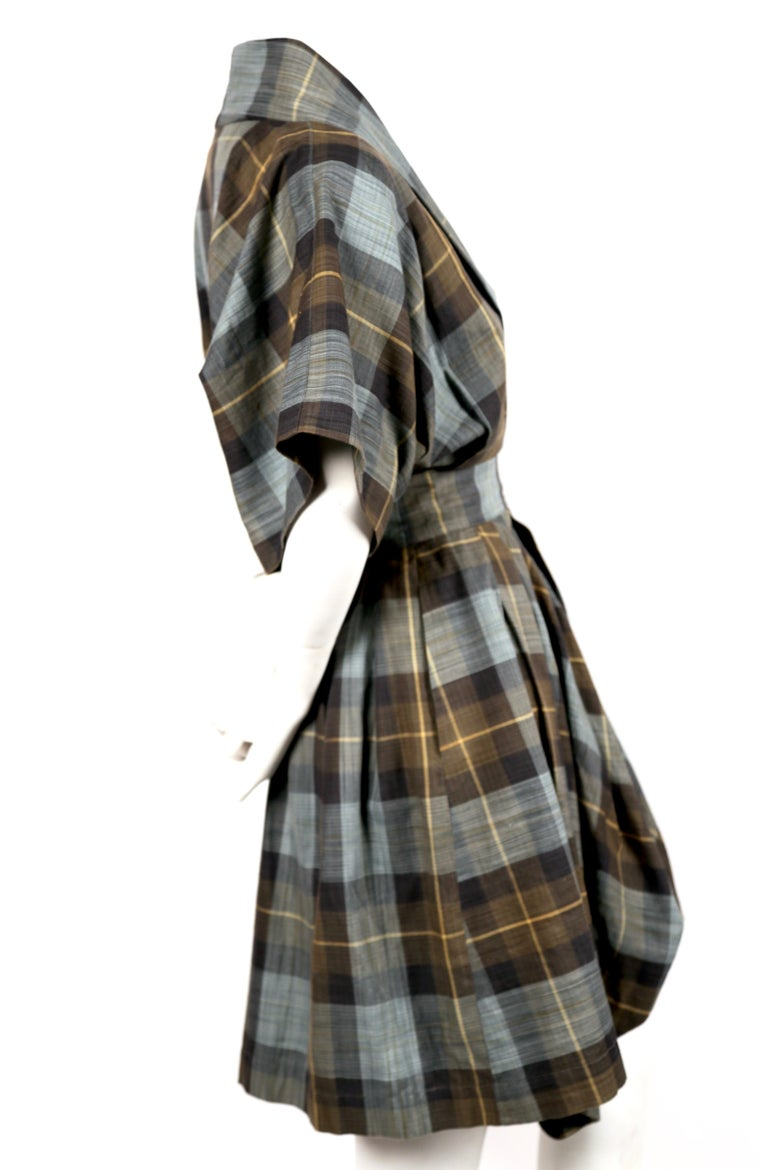 Plaid cotton dress with wrap closure and draped hemline designed by Issey Miyake dating to the early 1980's. Labeled a size M however this would best fit a US XS. Approximate measurements: waist 24