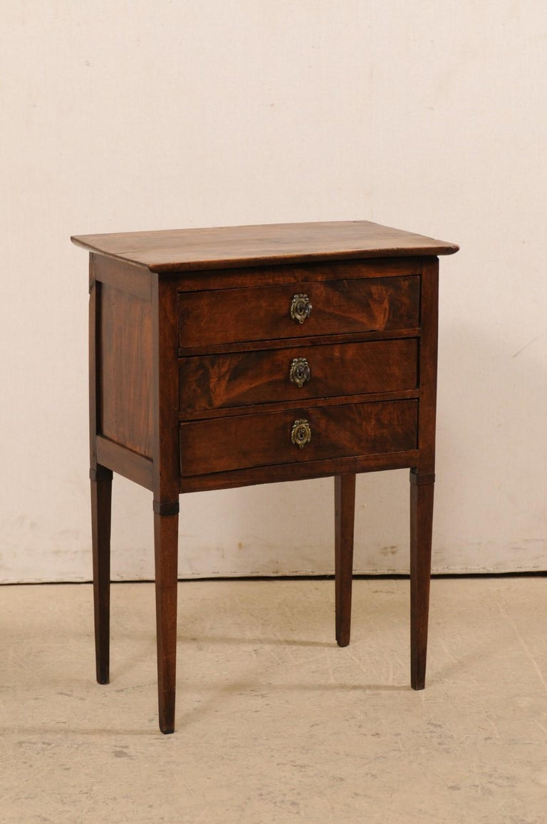 A French raised side chest with drawers from the early 19th century. This antique side chest or end-table from France features nice clean lines, allowing the beautiful wood grain to speak for the simple elegance of this piece. The chest houses three