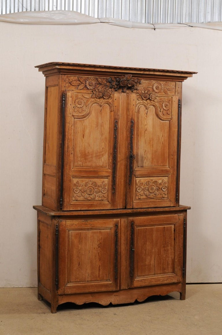A French tall carved-wood, four-door cabinet from the early 19th century. This antique cabinet from France, which stands approximately 7.25 ft tall, has been designed with a sweetly carved floral motif, which is emphasized with the three-dimensional
