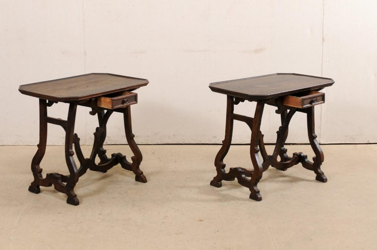 An Italian pair of carved walnut wood side tables, with single drawer, from the early 19th century. This pair of antique tables from Italy each feature mostly rectangular-shaped tops with four cut corners and slightly raised lip, with a single