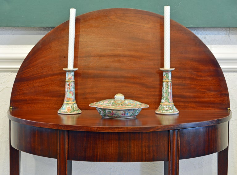 This distinguished Georgian game table is made of the very best mahogany and features a folding top that opens up to a circular table. With the top half open and leaning against a wall a beautiful display area is created. The table rests on four
