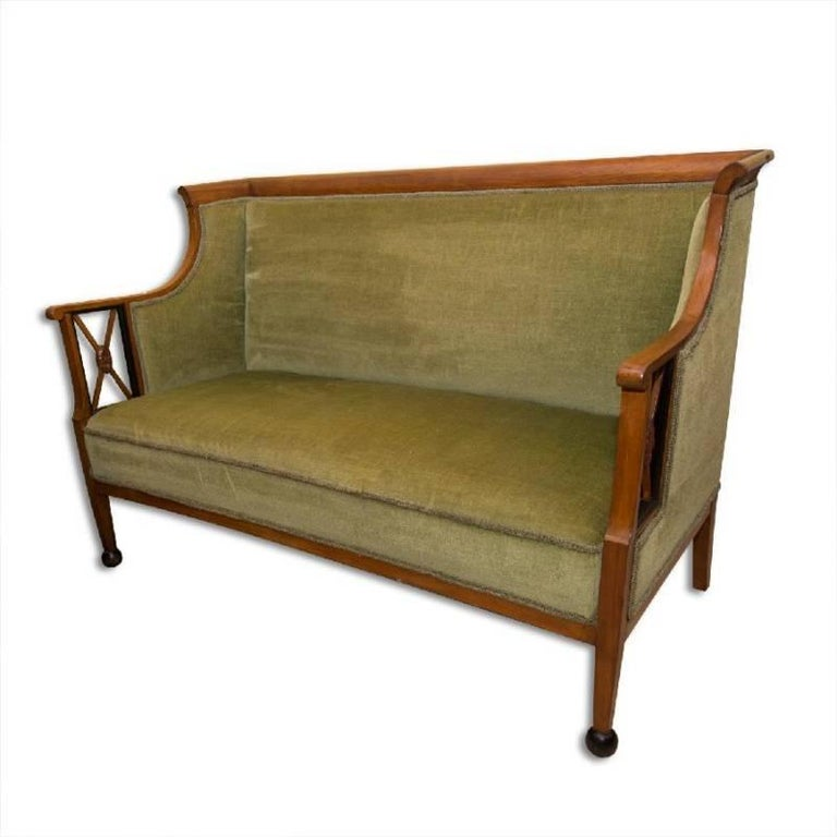 This antique sofa from the Biedermeier period was made circa 1830 in Austria. It features carved walnut veneer and is upholstered with a suede fabric. It is in good condition, it has been renovated in the past.