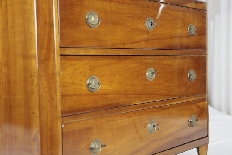 A simple and straight chest of drawers from the Biedermeier period, made around 1820-1930 in cherry veneer on softwood, partly solid cherry. The chest of drawers has 3 spacious drawers with brass fittings and a middle key. The front corners of the