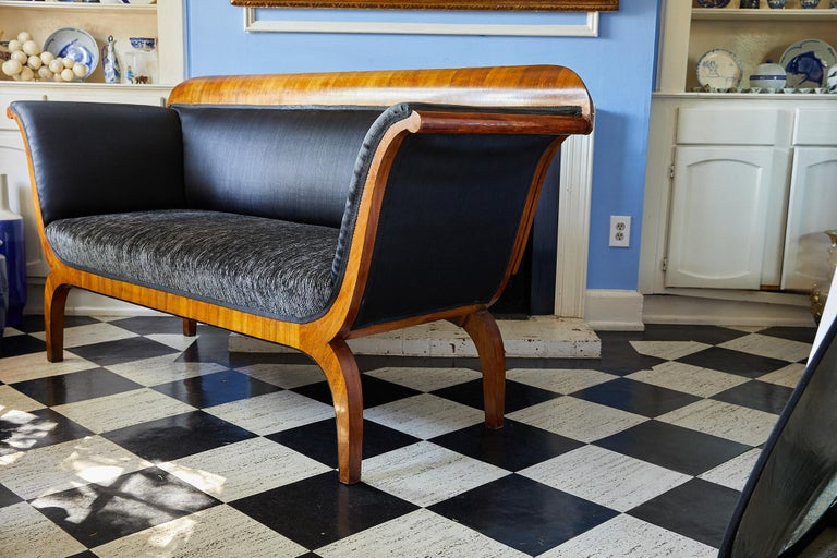 Early 19th century Biedermeier period sofa of elegant proportions. The sofa's crest rail, upswept arms, apron, and curved legs are veneered in Cherrywood. The arms and tight back of the sofa are upholstered in sleek black horsehair fabric while the