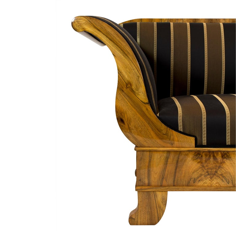 The sofa dates from the Biedermeier period at the beginning of the 19th century. The body of the sofa is made of spruce wood and was covered with a very beautiful walnut veneer, which was mounted mirrored. The sofa is in very good condition. The