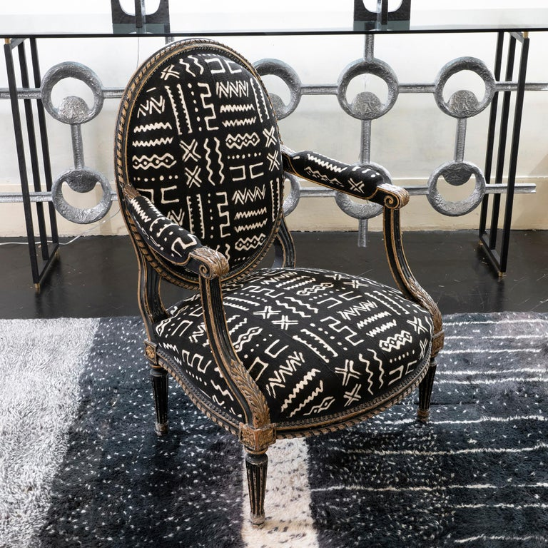 Early 19th century Italian armchair, black and gilded newly reupholstered with a black and white ethnic print cotton fabric.