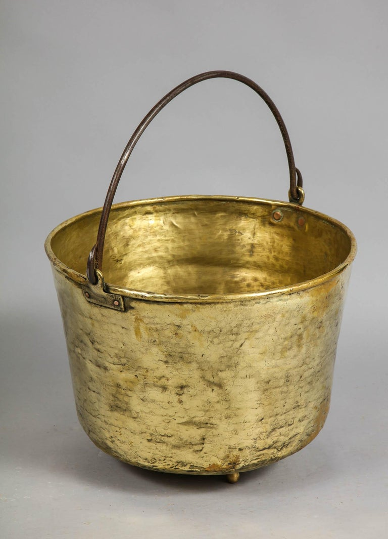 Fine early 19th century hand-hammered brass pail having wrought iron handle with rat tail curled ends, the body with nicely beated surface, the base with later brass ball feet for sitting firmly (not rocking) on the hearth. Originally probably made