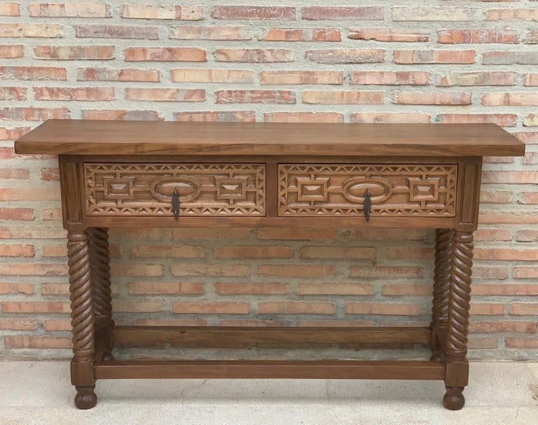 A 19th century walnut console table with a slab top above a frieze with two drawers with front decorated with carved geometrical motifs and incised with additional decoration and a single iron pull in each drawer. The table is supported on a hand