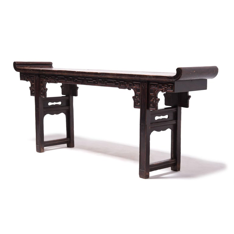 """In ancient China slender, long tables like such as this one are often referred to as """"altar tables"""" and used to hold musical instruments, flowers, or vases. This 150-year-old table was carved in China's Shanxi province. It has averted ends curving"""