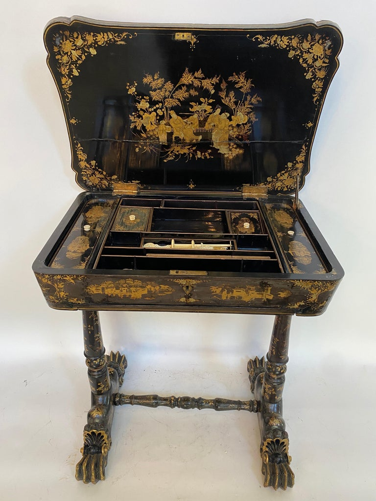 Early 19th century Chinese export lacquer and gilt sew working table from the Qing dynasty, with carved gilt dragon head feet, with the table of canted rectangular form, with mounded top, the entire finely decorated with the typical figural