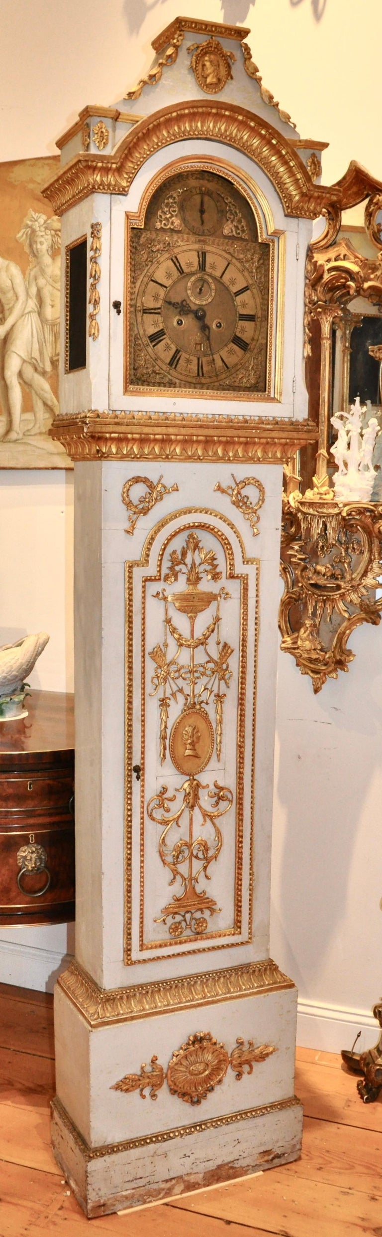 Early 19th century Danish carved and giltwood neoclassical tall case clock. Original gilding on all hand carved neoclassical ornamentation. Palace provenance, more than likely. Profile of each a man and a woman, most likely nobility or from the