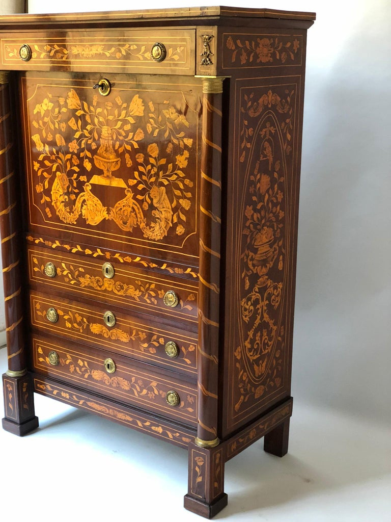 An early 19th century Dutch mahogany and satinwood foliate marquetry secretaire a abattant with fall front enclosing a well fitted interior of short drawers and gilt tooled green leather writing surface(which holds solidly at the horizontal and