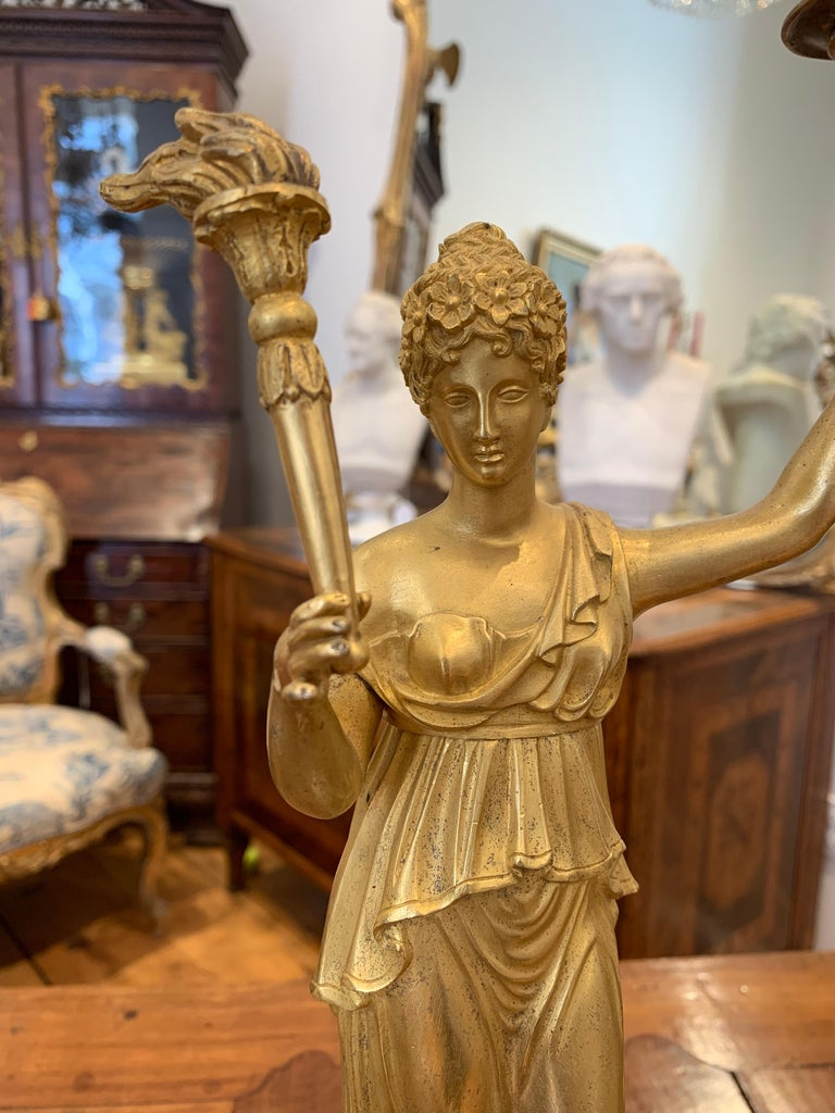 Early 19th century gilt bronze and marble candlestick or candelabrum. Of neoclassical form, a woman holding a torch to light an urn with candle. Great gold quality.