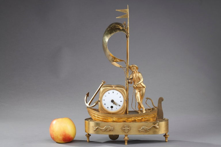Small mantel clock The Sailor crafted of ormolu, or gilt bronze, in the early 19th century, featuring a European sailor carrying a bale of cotton on the sea. The round enamel dial features Roman numeral hours, indicated by means of two pierced gilt