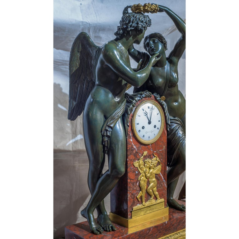 A fine quality empire ormolu-mounted patinated bronze and rouge royale marble mantel clock.