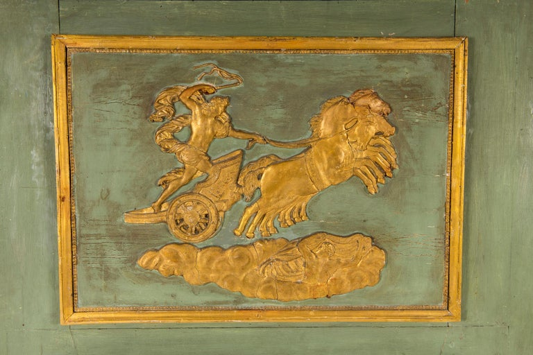 An early 19th century painted and parcel-gilt Empire trumeau mirror with horse and chariot scene.