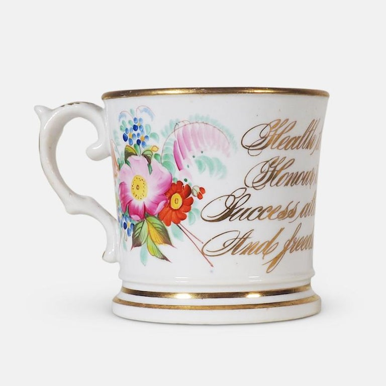 An important early 19th century English ceramic anti-slavery cup. Slightly tapered form, with bright gilt borders and hand painted with floral sprigs flanking abolitionist script: 'Health to the sick, honour to the brave, success attend, true love
