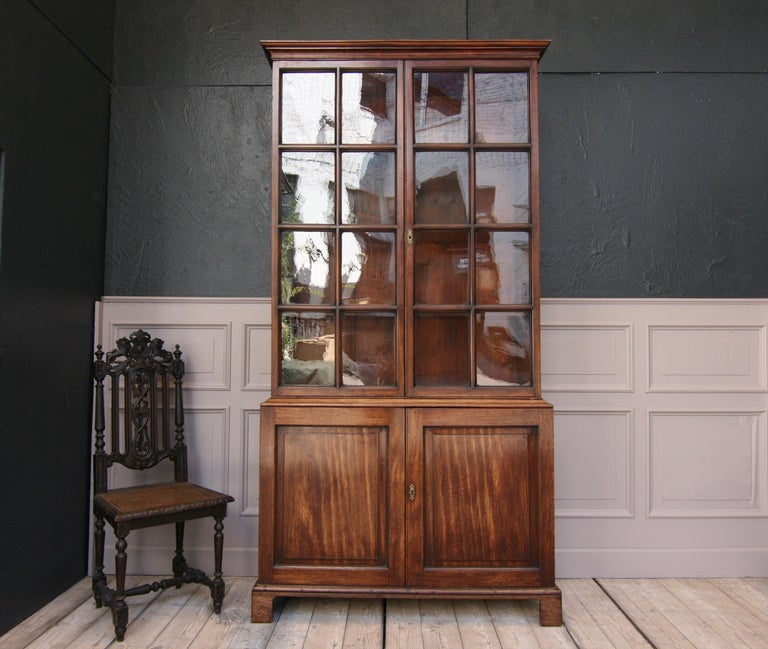English mahogany bookcase or china cabinet, circa from the early 19th century.  Consisting of a base cabinet with 2 doors and a tall display case, also with 2 doors (with the original mouth blown glass), with 3 adjustable