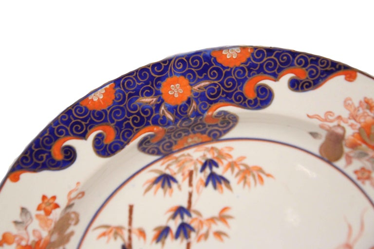Early 19th century English ironstone charger, the border with a multitude of flowers and foliate on alternating cobalt and ivory backgrounds, the center featuring bamboo, floral and foliate motifs. Photos note minor gilding loss to center flower and