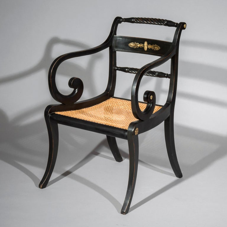 An early 19th century Regency period black painted and brass mounted desk armchair of Greek revival Klismos form, in the taste of Thomas Hope.  English, circa 1810.  This black-japanned and cane-seated chair, with Grecian boldly curved legs and