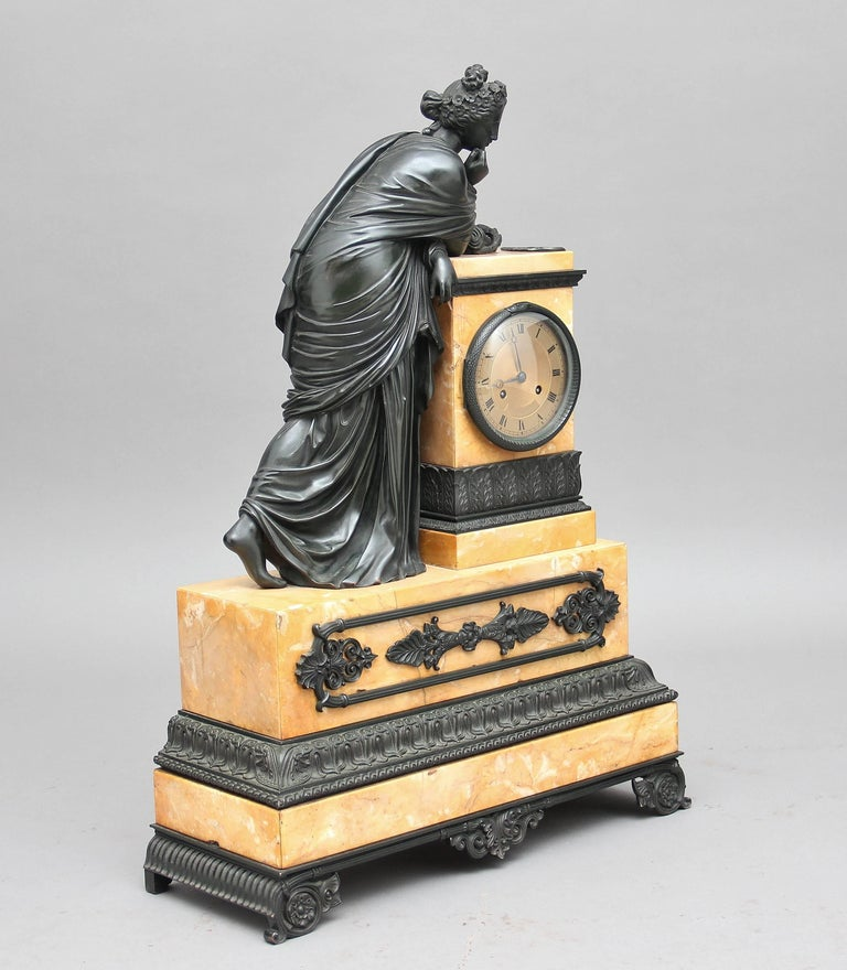 A fabulous quality French bronze and marble mantle clock, this imposing clock is of a classical Greek maiden leaning on a marble column that incorporates the clock, the lady and the column are on a marble plinth standing on bronze feet, the marble