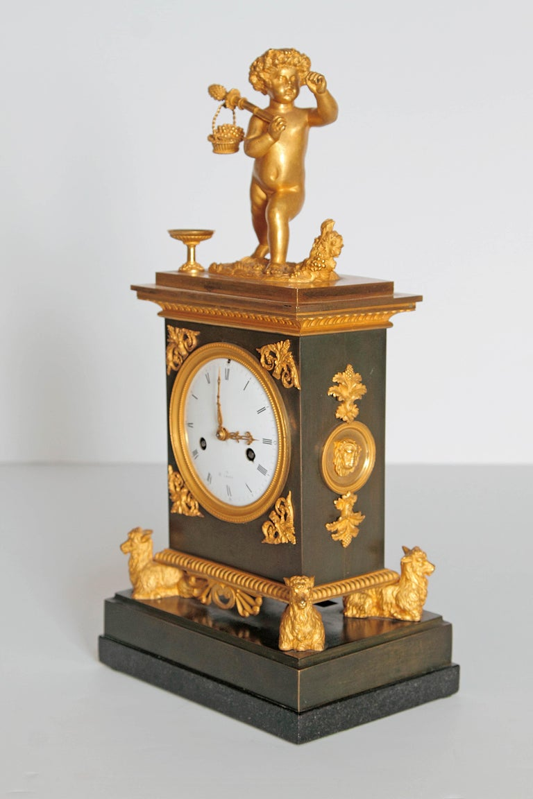 An elegant French black marble clock with gilt bronze embellishments. Four gilt goats on base support the clock. Gilt mounts on sides have lions heads. A large putto with basket of fruit is on the top, enameled round white face. Early 19th century,