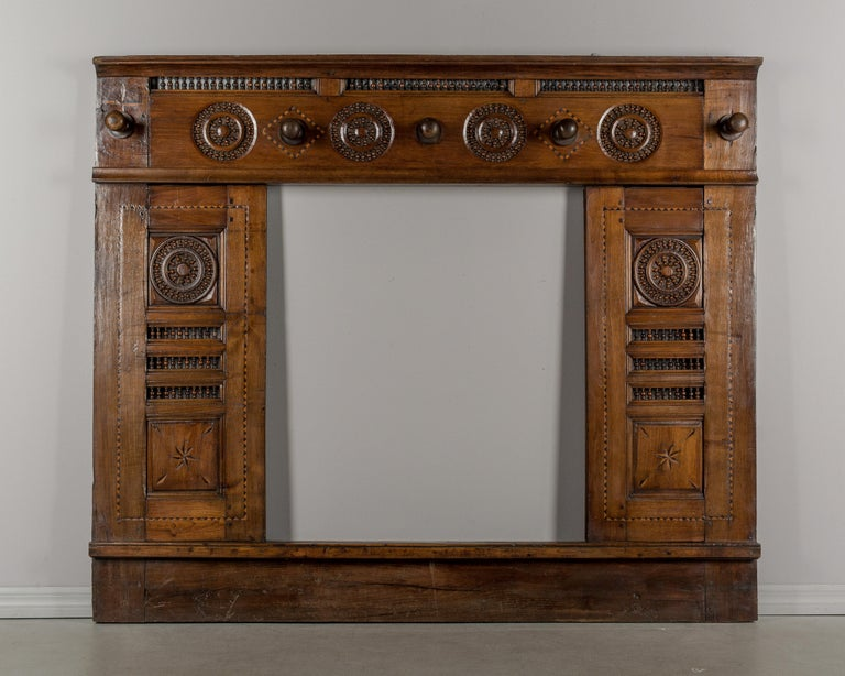 An early 19th century French hall tree made of chestnut. This was originally the front framework of a traditional Brittany lit clos (enclosed bed). The cabinet doors have been removed and five large pegs were added at the top to hang coats and hats.
