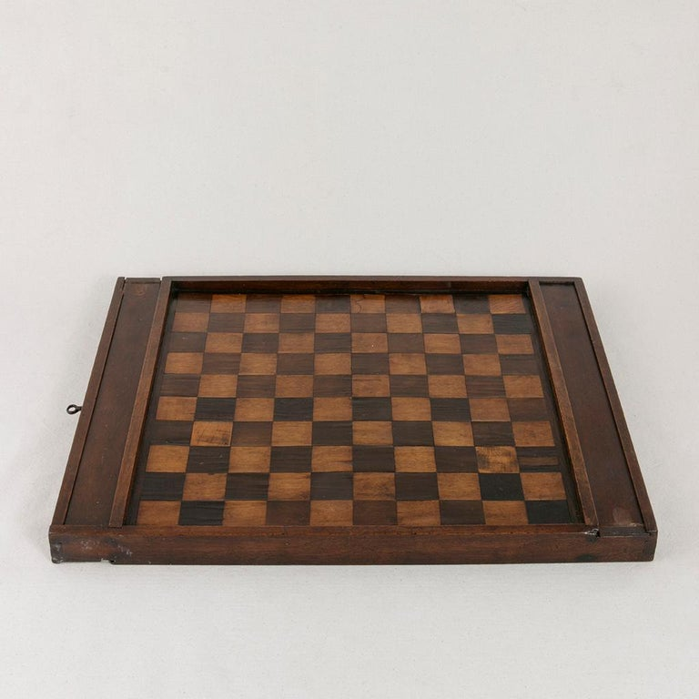 This early 19th century walnut and ebonized pear wood marquetry game board is double sided and features a chess and checker board playing surface on one side and a more traditional 10 x 10 draughts board on the other side. Two sliding compartments