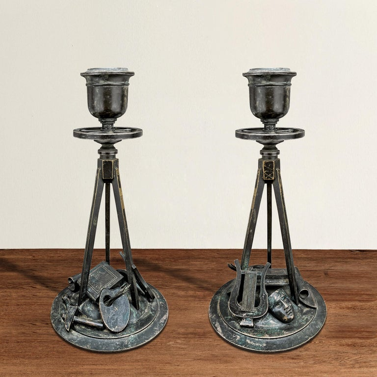 An incredible pair of spirited early 19th century French Empire bronze candlesticks celebrating the arts with individually cast and applied painters' palettes with brushes, sculptors' hammers and compasses, writers' books, musicians' harps, drama