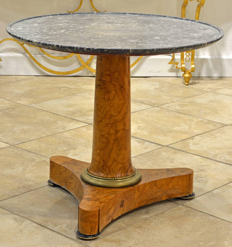 An iconic and distinguished design characterizes this table featuring a black/gray/white dish-carved marble top supported by a single conical stem and gilt bronze foot resting on a three pointed base with gilt bronze and ebonized feet.
