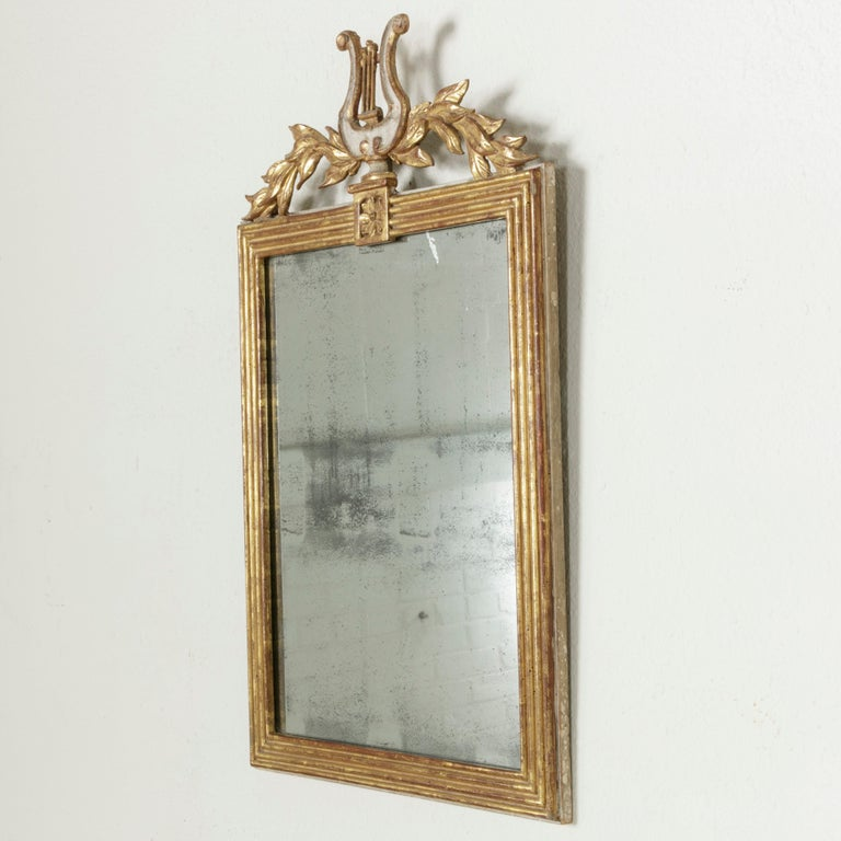 From the time of Napoleon Bonaparte, this French Empire period giltwood mirror from the early 19th century features a sculptural lyre flanked by laurel branches. Its original mercury glass is surrounded by a square fluted frame with a single rosette