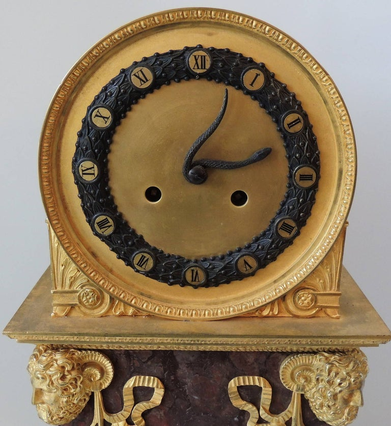 This early 19th century Empire style figural clock with a snake as the hands on the clock is set on wonderful rouge marble and a pedestal base. The four corners are marked with four wonderfully detailed doré bronze figure heads, The front is
