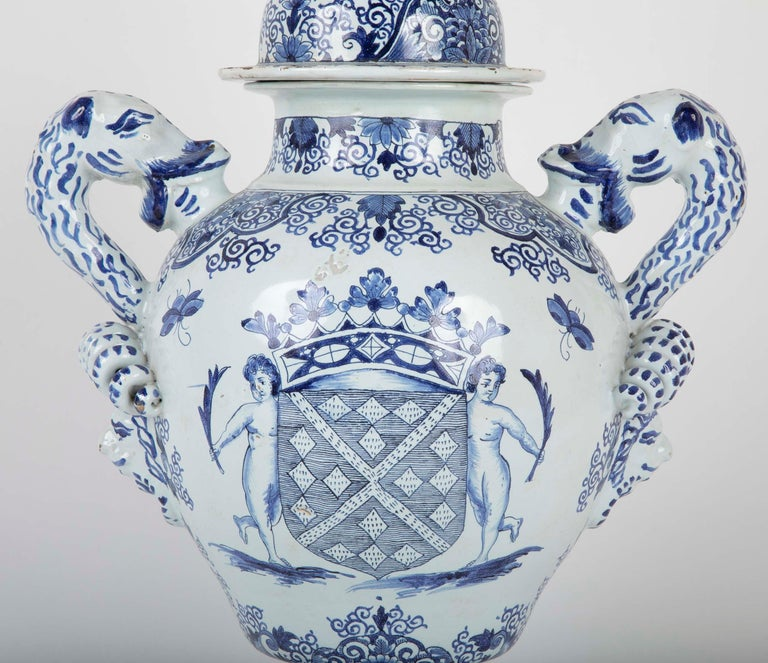 An early 19th century French faience lidded jar; probably Rouen. Painted with a heraldic crest. Delft style.